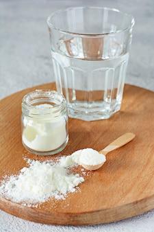 Kolagen w proszku ze szklanką wody na jasnym tle. dodatkowe spożycie białka. naturalne piękno i zdrowie suplement dla skóry, kości, stawów i jelit.