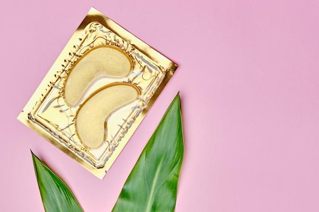 Kolagenowe złote kosmetyczne plastry pod oczy i zielone liście. koncepcja pielęgnacji skóry i kosmetologii.