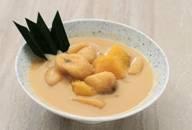 Kolak pisang ubi lub kompot z bananów i słodkich ziemniaków to popularny indonezyjski deser zrobiony z bananowych słodkich ziemniaków gotowanych z mlekiem kokosowym, cukrem palmowym i liśćmi pandanu. popularne podczas ramadanu