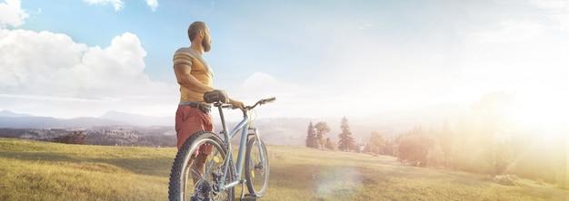 Kolarstwo mężczyzna z rowerem na leśnej drodze w górach na letnim dniu. górska dolina podczas wschodu słońca.