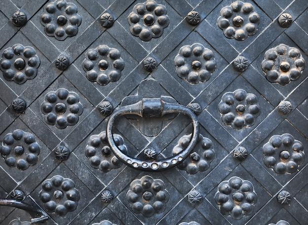 Kołatka ręka na starych drzwiach. stare miasto tło i tekstura