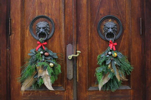 Kołatki do drzwi z brązowej głowy lwa ozdobione świątecznymi wieńcami. wieńce bożonarodzeniowe na drzwiach drewnianych