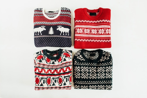 Kolaż ciepłych wełnianych swetrów na białej powierzchni. widok z góry na płasko