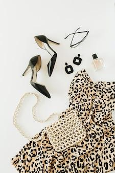 Kolaż z nowoczesnymi ubraniami i akcesoriami dla kobiet. sukienka w panterkę, buty na wysokim obcasie, kolczyki, okulary, torebka, perfumy na białym tle