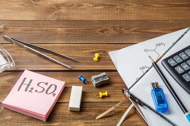 Kolby chemiczne, pincety, klawiatura, zeszyty na drewnianym stole z copyspase.