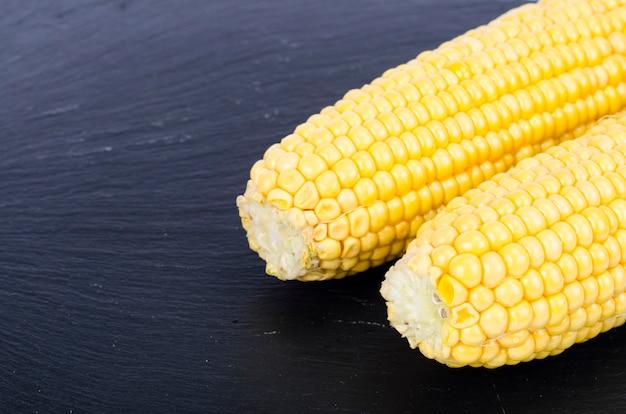 Kolby dojrzałej żółtej kukurydzy cukrowej na czarnym tle. zdjęcie studyjne.