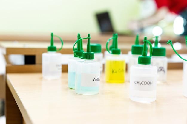 Kolby przemysłu chemicznego z płynnymi probówkami laboratoryjnymi znajdują się na stole w laboratorium