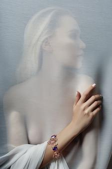 Kolczyki i biżuteria w uchu seksownej kobiety wkładanej przez przezroczystą tkaninę