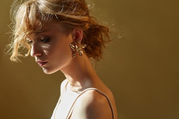 Kolczyki i biżuteria w uchu wytłoczonej seksownej blondynki. idealna blondynka, cudowny tajemniczy wygląd. biżuteria reklamowa, piękne kolczyki w uchu dziewczynki. skopiuj miejsce