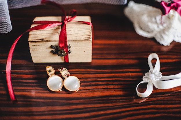 Kolczyki, pudełko i podwiązka na brązowym stole