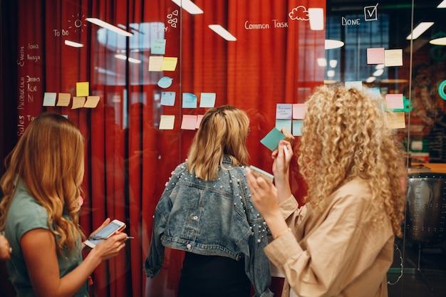Koledzy biznesowi ludzie kobiety pisanie na karteczkę na szklanej ścianie ze współpracownikami stoją w biurze. planowanie i analiza pracy zespołowej oraz zarządzanie czasem
