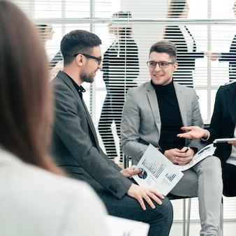 Koledzy biznesowi omawiający dane finansowe w sali konferencyjnej. pomysł na biznes