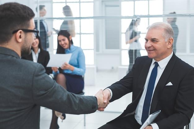 Koledzy biznesowi podają sobie ręce siedząc w sali konferencyjnej. koncepcja współpracy