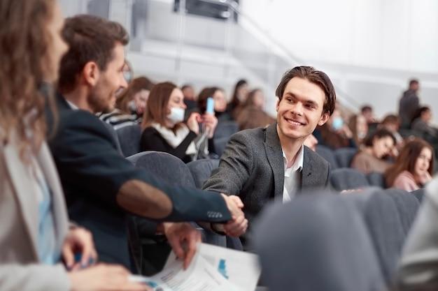 Koledzy biznesowi ściskają sobie ręce w sali konferencyjnej