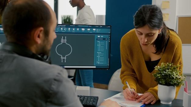 Koledzy dyskutują o projekcie przemysłowym analizując koła zębate 3d patrząc na komputer z oprogramowaniem cad i pisząc na karteczkach samoprzylepnych