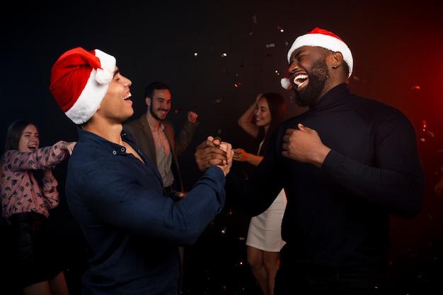 Koledzy gratulują sobie nawzajem na przyjęciu noworocznym