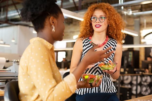 Koledzy jedzą. kręcona stylowa rudowłosa kobieta w naszyjniku je sałatka z kolegą