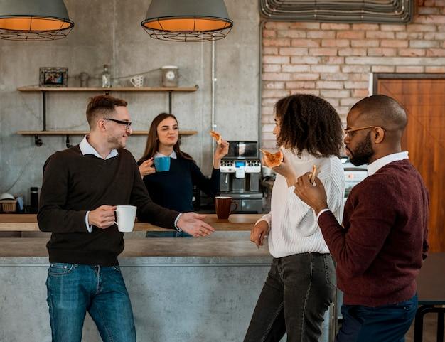 Koledzy jedzą pizzę i kawę podczas przerwy na spotkanie w biurze
