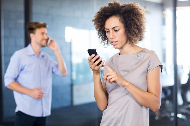 Koledzy komunikowania się na telefon komórkowy przed salą konferencyjną w biurze