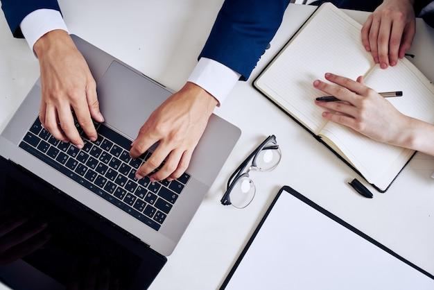 Koledzy laptop i dokumenty na technologii stołu