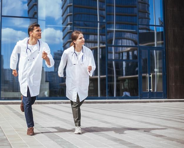 Koledzy lekarze biegną ulicą miasta na wezwanie pomocy. zdjęcie z przestrzenią do kopiowania.