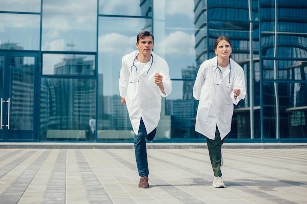 Koledzy lekarze biegną ulicą miasta na wezwanie pomocy