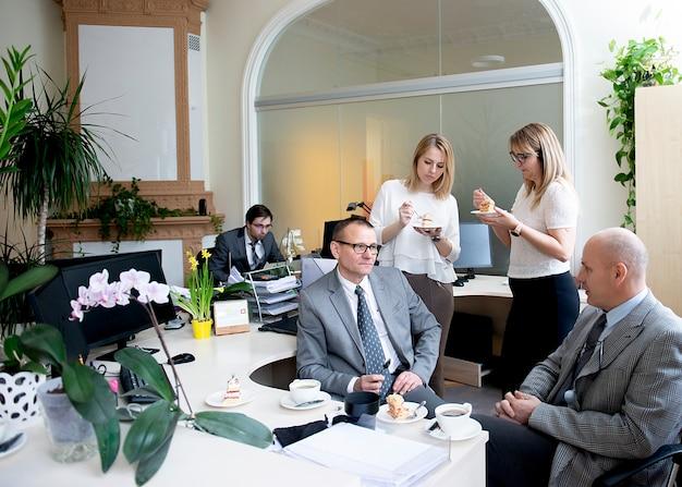Koledzy mają przerwę na kawę w biurze przy biurku