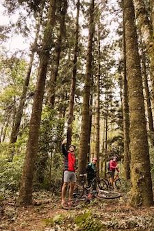 Koledzy na rowerze robią sobie selfie w lesie