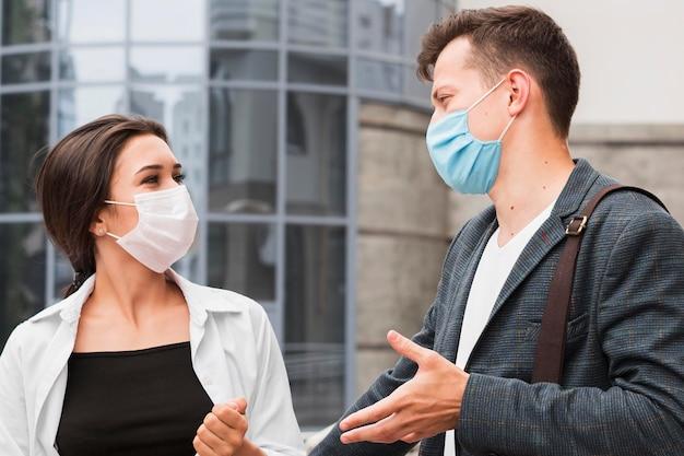 Koledzy na zewnątrz podczas pandemii, rozmawiając w maskach na twarz
