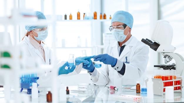 Koledzy naukowcy sprawdzający płyn w kolbach laboratoryjnych