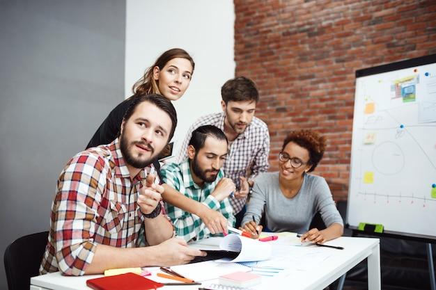 Koledzy omawiają nowe pomysły na spotkaniu biznesowym.