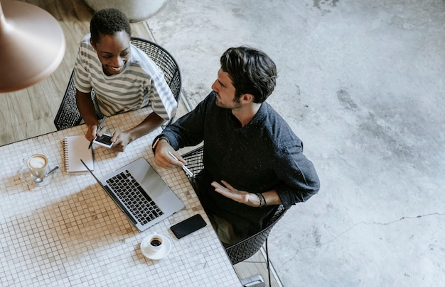 Koledzy omawiają swoją pracę na laptopie