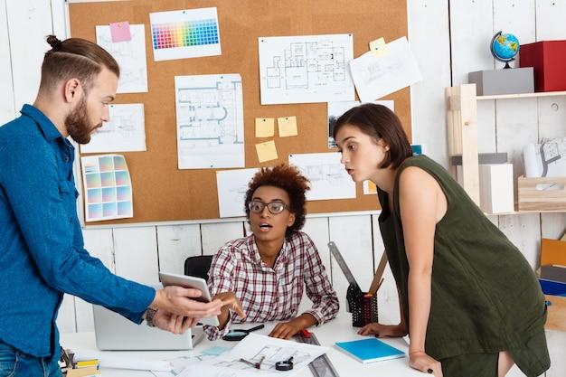 Koledzy, patrząc na tablet, omawiając nowe pomysły w biurze