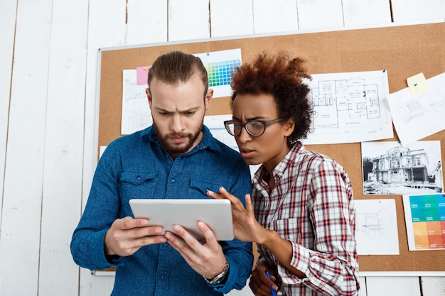Koledzy patrząc na tablet, omawiając nowe pomysły