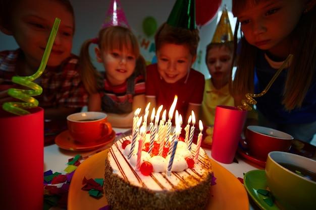 Koledzy patrząc na tort urodzinowy ze świecami
