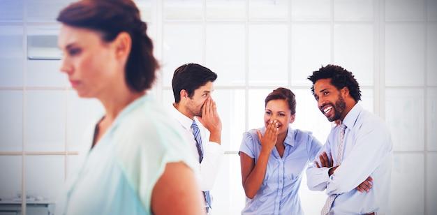 Koledzy plotkują ze smutną bizneswoman na pierwszym planie