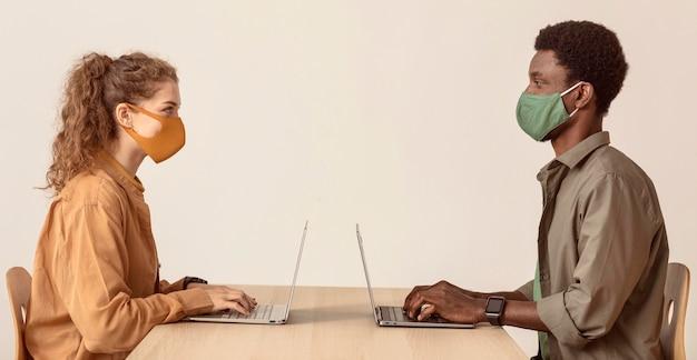 Koledzy pracujący na laptopach i noszący maski
