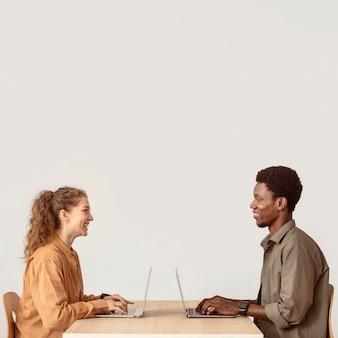 Koledzy pracujący na swoich laptopach kopiują przestrzeń