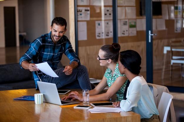 Koledzy pracujący przy biurku komputerowym