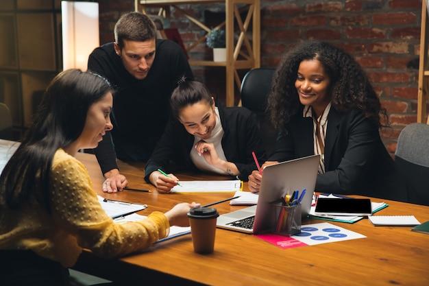 Koledzy pracujący razem w nowoczesnym biurze przy użyciu urządzeń i gadżetów podczas kreatywnych spotkań