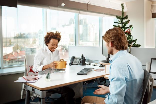 Koledzy pracuje w biurze na boże narodzenie daje prezenty.