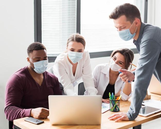 Koledzy przy pracy w biurze podczas pandemii patrząc na laptopa z maskami