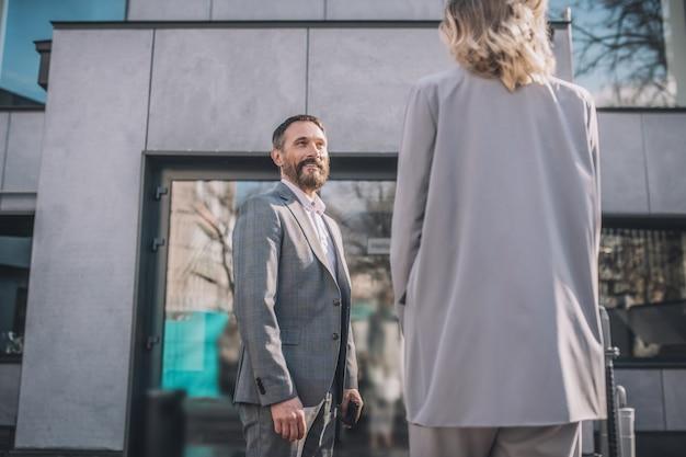 Koledzy. radosny dorosły biznesmen w szarym garniturze szuka zainteresowanych i kobieta z powrotem do aparatu na ulicy