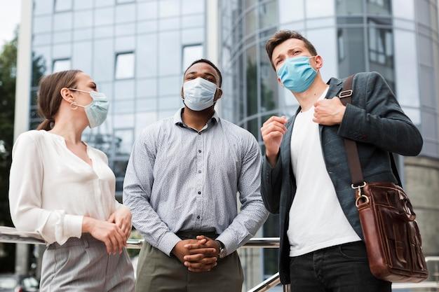 Koledzy rozmawiają na zewnątrz podczas pandemii w maskach medycznych