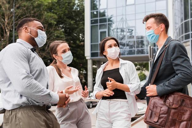 Koledzy rozmawiają na zewnątrz podczas pandemii z maskami na twarz