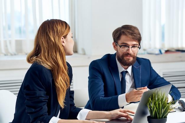 Koledzy rozmawiają przy stole przed laptopem team technology. zdjęcie wysokiej jakości