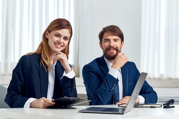 Koledzy rozmawiają przy stole przed laptopem w technologii biurowej