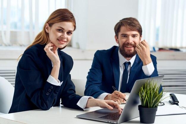 Koledzy rozmawiają przy stole przed technologią laptopów profesjonalistów