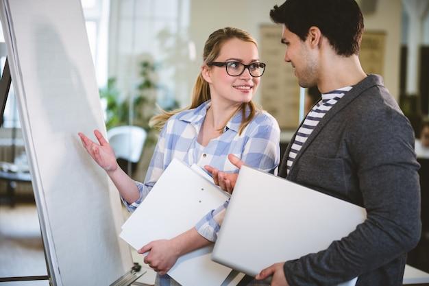 Koledzy rozmawiają tablicą w biurze kreatywnym