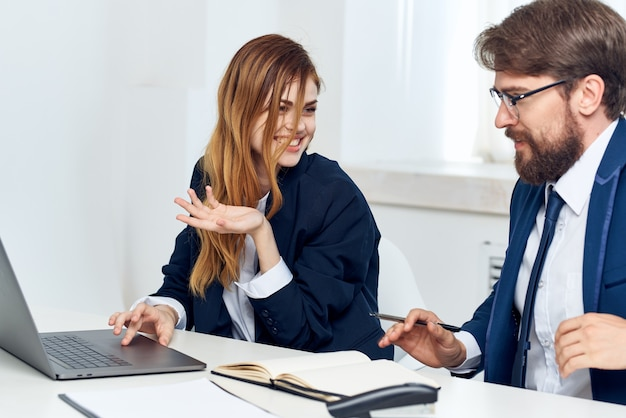 Koledzy rozmawiający w biurze przed laptopem profesjonaliści